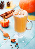 Pumpkin smoothie, spice latte with whipped cream. Turquoise wooden background. Stock Photography