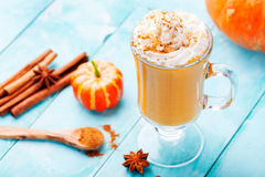 Pumpkin smoothie, spice latte with whipped cream. Turquoise wooden background. Pumpkin smoothie, spice latte with whipped cream on top on a turquoise wooden Royalty Free Stock Photo