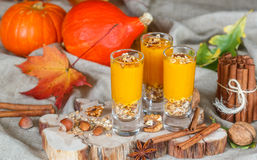 Pumpkin smoothies with nuts, cinnamon, ginger and granola. Useful nutrition. Autumn desserts. Selective focus stock image
