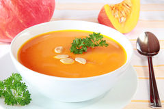 Pumpkin Soup. Bowl of pumpkin soup and pumpkins in the background royalty free stock images