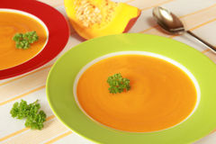 Pumpkin Soup. Two Bowls of pumpkin soup and a pumpkin in the background stock photo