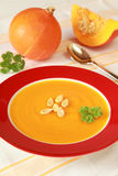 Pumpkin Soup. Bowl of pumpkin soup and pumpkins in the background royalty free stock image