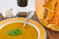 Pumpkin soup. A bowl of pumpkin soup with a couple of basil leaves, pepper, garlic and a Halloween pumpkin Stock Photos