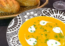 Pumpkin Soup. Served in black and white bowl with fresh bread rolls Stock Image
