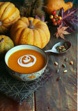 Pumpkin soup. Autumn pumpkin soup with seeds on a wood table Royalty Free Stock Image