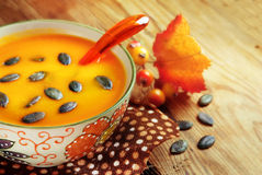 Pumpkin soup. Autumn pumpkin soup with seeps on a wood table Stock Photography