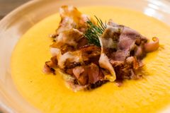 Pumpkin soup with bacon decorated with greenery royalty free stock image