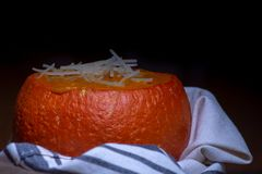 Pumpkin soup in baked mini-pumpkin wrapped in white dish cloth against black. Pumpkin soup served in baked mini-pumpkin wrapped in white dish cloth against black stock photo