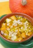 Pumpkin soup with barley. In green ceramic pot Stock Photos