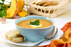 Pumpkin soup in a blue cup. Sliced ​​squash and corn on the background Stock Image