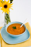 Pumpkin soup in a blue plate and a bouquet of flowers Royalty Free Stock Photos