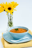 Pumpkin soup in a blue plate and a bouquet of flowers Royalty Free Stock Photography