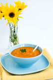 Pumpkin soup in a blue plate and a bouquet of flowers Royalty Free Stock Photo