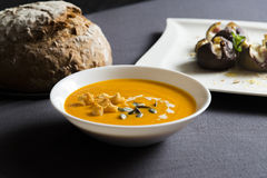 Pumpkin soup in a bowl with bread and roasted figs with goat cheese Stock Photo