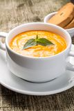 Pumpkin soup in bowl with fresh basil Stock Photo