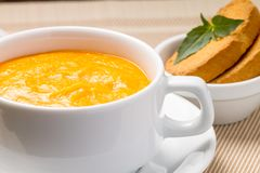 Pumpkin soup in a bowl with fresh basil Stock Photo