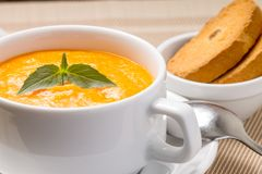 Pumpkin soup in a bowl with fresh basil Stock Photography