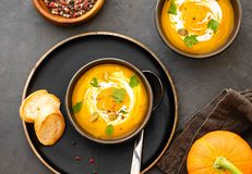 Pumpkin soup in a bowl with fresh pumpkins, garlic and parsley herbs on a black background. Autumn concept. Pumpkin soup in a bowl with fresh pumpkins, garlic stock photography