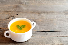 Pumpkin soup in bowl isolated on old wooden background with blank space for text. Simple pumpkin soup recipe. Vegetable dish. Vegetable soup photo. Vegetarian Royalty Free Stock Image