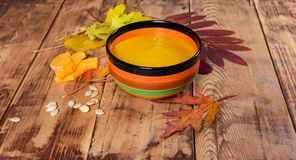 Pumpkin soup bowl on rustic wooden background Royalty Free Stock Photos