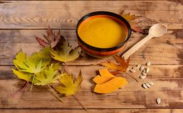 Pumpkin soup bowl on rustic wooden background Royalty Free Stock Images