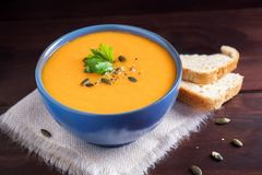 Pumpkin soup in a bowl served with parsley, olive oil and pumpkin seeds. Vegan soup. Dark wooden background royalty free stock photo