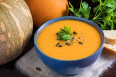 Pumpkin soup in a bowl served with parsley, olive oil and pumpkin seeds. Vegan soup. Dark wooden background stock photos