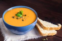 Pumpkin soup in a bowl served with parsley, olive oil and pumpkin seeds. Vegan soup. Dark wooden background royalty free stock photography