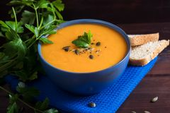 Pumpkin soup in a bowl served with parsley, olive oil and pumpkin seeds. Vegan soup. Dark wooden background royalty free stock images