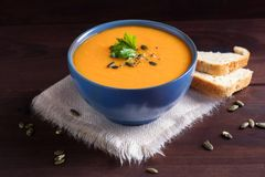 Pumpkin soup in a bowl served with parsley, olive oil and pumpkin seeds. Vegan soup. Dark wooden background stock photo