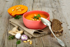 Pumpkin soup in bowl on wooden background Royalty Free Stock Images