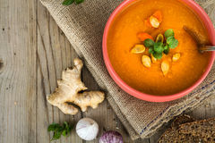 Pumpkin soup in bowl on wooden background Stock Images