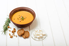 Pumpkin soup with bread crouton on white wooden table. Pumpkin soup with bread crouton on the white wooden table Royalty Free Stock Images