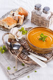 Pumpkin soup with bread and garlic on white tablecloth. Bowl of creamy pumpkin soup with rustic bread and garlic in a woven plate on a white tablecloth royalty free stock images