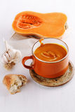 Pumpkin soup, bread and garlic on white wooden background Stock Images