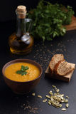 Pumpkin soup, bread and olive oil on the black table Stock Image