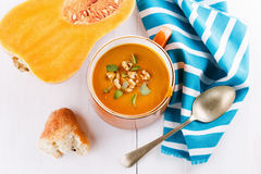 Pumpkin soup with bread and squash on white background. Bowl of creamy pumpkin soup with a piece of rustic bread and butternut pumpkin on a white background stock photo