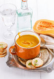 Pumpkin soup with bread on white background. Bowl of creamy pumpkin soup with croutons and butternut pumpkin on a white wooden background. Selective focus stock image