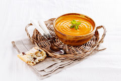 Pumpkin soup with bread on white tablecloth. Bowl of creamy pumpkin soup with rustic bread and spoons in a straw plate on a white tablecloth stock photo