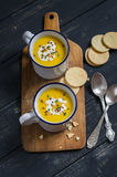 Pumpkin soup in ceramic mugs on a wooden surface Royalty Free Stock Images