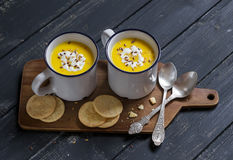 Pumpkin soup in ceramic mugs on a wooden surface Royalty Free Stock Photo