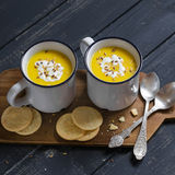 Pumpkin soup in ceramic mugs on a wooden surface Royalty Free Stock Photos