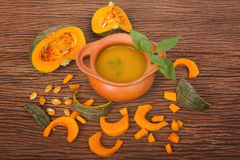 Pumpkin soup in clay pot with fresh pumpkins Royalty Free Stock Images