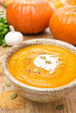 Pumpkin soup with coriander and cream in a bowl, vertical Royalty Free Stock Image