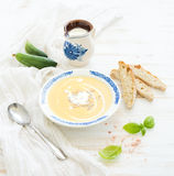 Pumpkin soup with cream, fresh basil, cucumbers. And bread in vintage ceramic plate over white wooden background Royalty Free Stock Photography