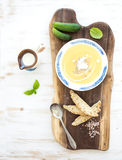 Pumpkin soup with cream, fresh basil, cucumbers. And bread in vintage ceramic plate on wooden board over white background, top view, copy space Stock Image