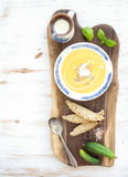 Pumpkin soup with cream, fresh basil, cucumbers. And bread in vintage ceramic plate on wooden board over white background, top view, copy space Royalty Free Stock Image