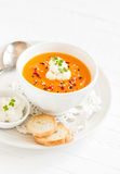 Pumpkin soup with cream and paprika in a white bowl Stock Photos