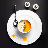Pumpkin soup with cream and pumpkin seeds in a white bowl over b Stock Image