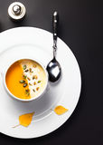 Pumpkin soup with cream and pumpkin seeds in a white bowl over b Royalty Free Stock Photo